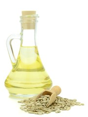 A bottle of sunflower cooking oil and seeds on white background