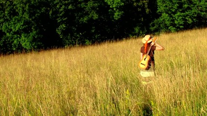 Hippie woman with hat and guitar walking in summer meadow