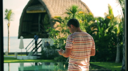 Man texting on cellphone and drinking coffee in luxury property