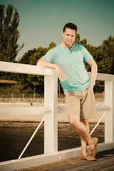 Fashion portrait of handsome man on pier