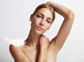 woman with an ideal armpit and feather on her shoulder