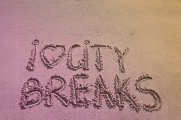 I Love City Breaks message written on sand, color filter applied