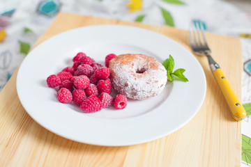 Breakfast. Donut with raspberries on plate