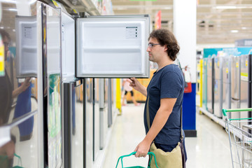 A man buys a refrigerator in the store