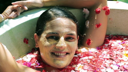 Woman with mask on her face smiling to the camera in the bath