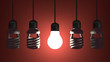 Glowing tungsten light bulb hanging among dead spiral ones