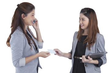 Two pretty businesswomen exchanging business cards