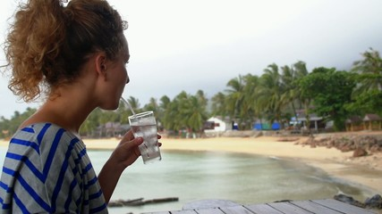 Young Woman Drinking Water in Restaurant against Palm Beach.