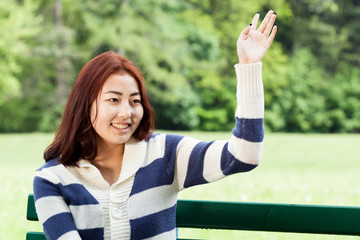 Girl sitting on bench, waving hand