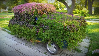 Fold car decorated with colorful flowers. Ecological concept