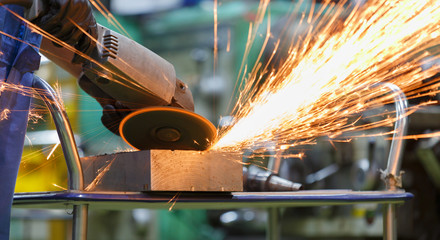 worker grinding steel by electric grinding machine