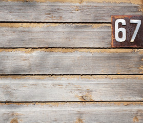 Old grungy wooden wall with house numbers