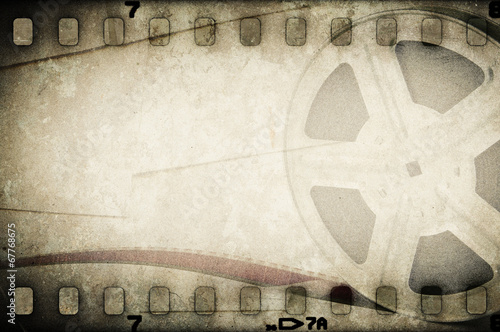 Grunge old motion picture film reel with film strip. - 67768675