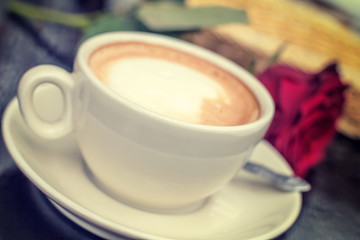 Blurred white cup of coffee with rose