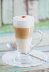 Frothy, layered cappuccino in a clear glass mug