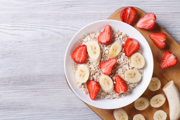 muesli with strawberries and banana with ingredients top view