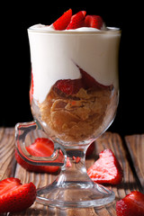 yogurt with strawberries and cornflakes on a dark background