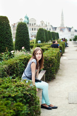 Young girl sitting in the garden of Mont des Arts in Brussels Be