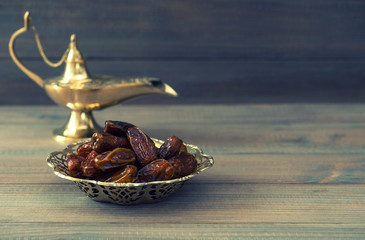 Dates in golden bowl and arabian lamp. Retro style toned picture