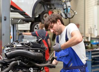 Mechaniker repariert Motor in Werkstatt // succesfull workman