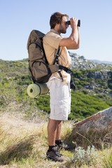 Handsome hiker looking through binoculars