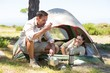 Outdoorsy couple cooking on camping stove outside tent
