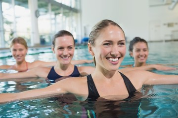 Female fitness class doing aqua aerobics