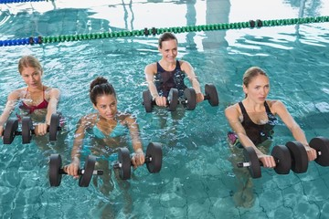 Female fitness class doing aqua aerobics with foam dumbbells