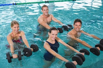 Happy fitness class doing aqua aerobics with foam dumbbells