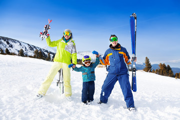 Positive parents in ski masks hold hands of son