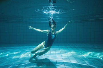 Athletic swimmer smiling at camera underwater