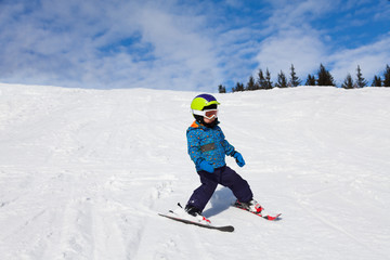 Boy in ski mask skiing on snow downhill