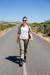 Pretty hiker walking on road and smiling at camera