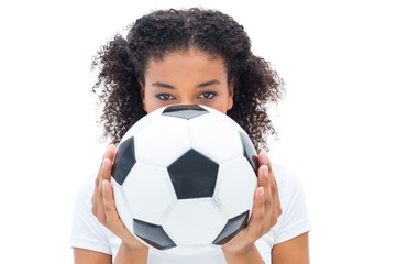 Pretty football fan in white holding ball over face