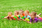 Kids play with water guns laying on a meadow