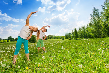 Boy and girl doing gymnastics on a meadow
