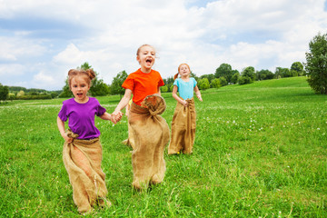Kids jump in sacks on a grass