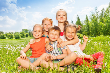 Five wonderful kids sitting together on a meadow