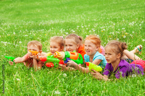 Kids play with water guns laying on a meadow - 67772879
