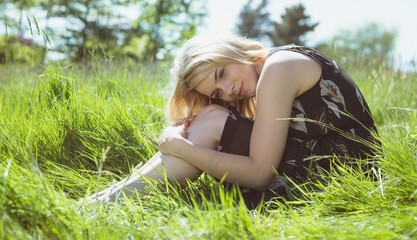 Pretty blonde in sundress sitting on grass