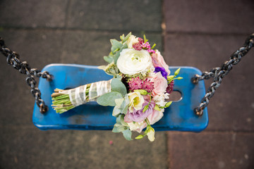 Bride bouquet on blue swing