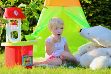 Happy toddler girl playing with toy kitchen outdoors
