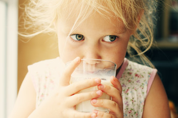 Cute cheerful little girl drinking milk