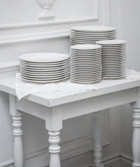 Set of clean plates at the white table.