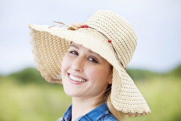 portrait of young lady in staw hat smiling at camera