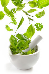 green herbs falling into mortar and pestle