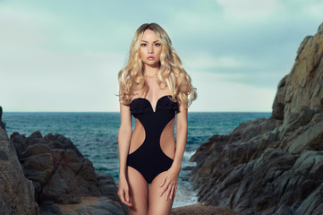 Lady in black swimsuit on seashore
