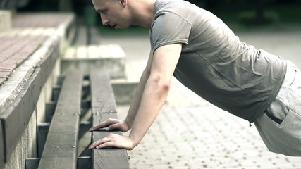Young man doing push-ups on bench in park