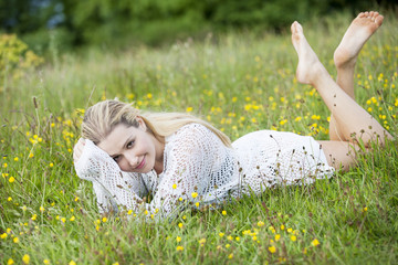 young lady posed in buttercups on grass