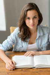 Student teenage girl reading book looking camera